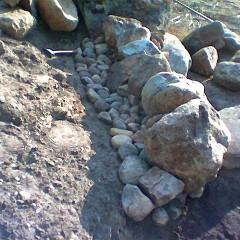 Toinen kerros kiviä lisätty. Taustan tuenta aloitettu.