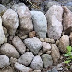 Reunakivien tausta tuettu erikokoisilla kivillä. Ensin suuremmat, sitten pienemmät ladottu.