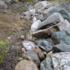 """Reunakivien alaosa tuettu. Pitkien kivien """"häntä"""" muurin sisälle päin."""