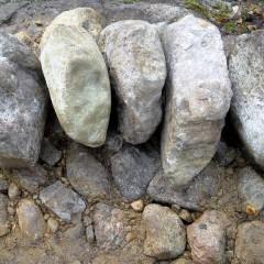 Toinen kerros alkaa. Kolme litteää pystyssä, pyoreämmät kivet tukevat.