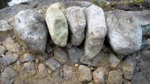 Kolme litteää pystyssä, pyoreämmät kivet tukevat reunoilla. Toisessa kivessä oikealta on 'häntä'. Se osoittaa muurin taustaan.